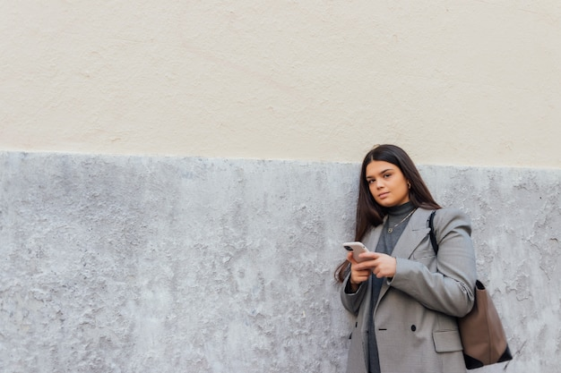 Mooie blanke vrouw die haar smartphone gebruikt terwijl ze tegen de muur leunt