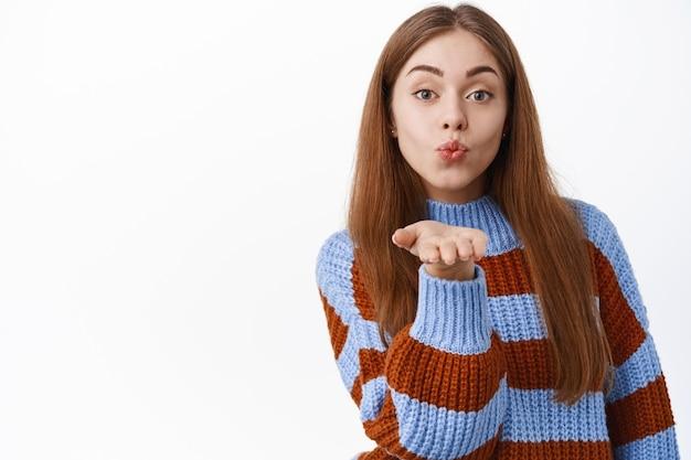 Mooie blanke vrouw die luchtkus verzendt, lippen tuit en palm bij de mond houdt, maakt mwah, staande in trui over witte muur