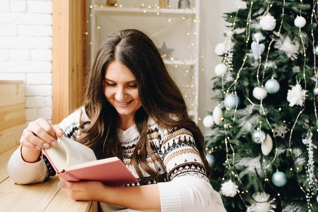 Mooie blanke vrouw die paars boek leest in de buurt van versierde kerstboom
