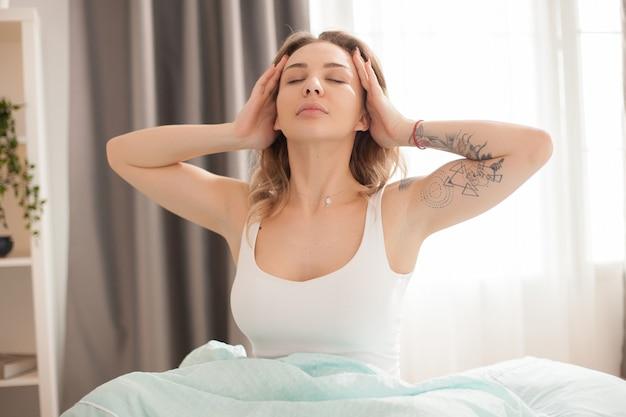 Mooie blanke vrouw die zich uitstrekt in de ochtend na het wakker worden met een pyjama.