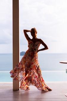 Mooie blanke vrouw in vliegende zomerjurk in het restaurant van de luxe hotelvilla op vakantie