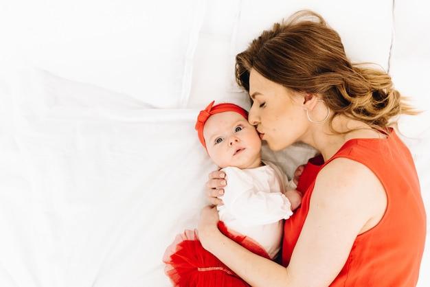 Mooie blanke vrouw kuste haar schattige baby dochter met ruimte voor tekst