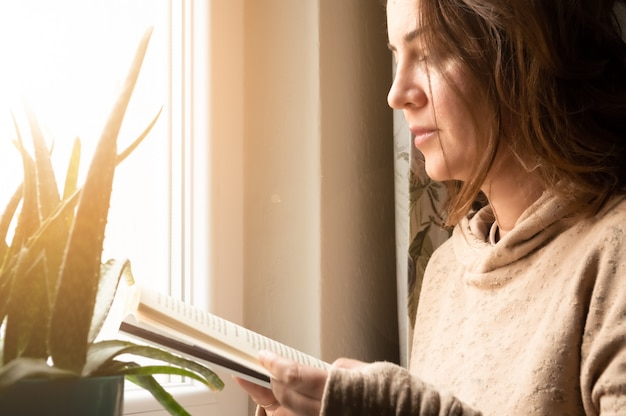 Mooie blanke vrouw leest een boek bij het raam op haar vrije tijd