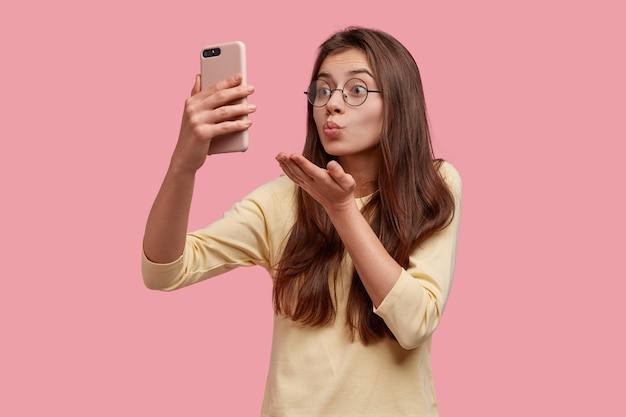 Mooie blanke vrouw maakt luchtkus op camera van mobiele telefoon, heeft videogesprek met vriendje op afstand, flirt en neemt afscheid