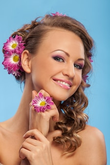 Mooie blanke vrouw met bloemen in haar