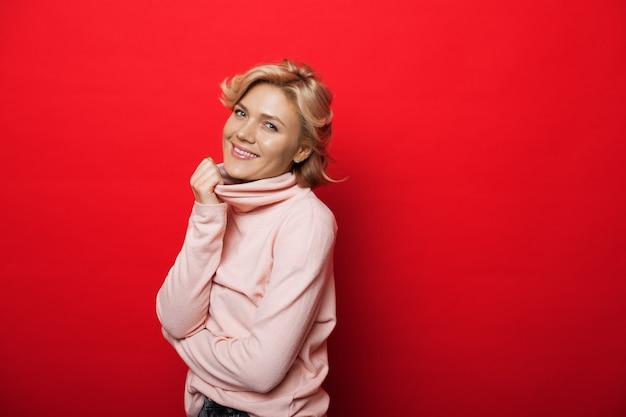 Mooie blanke vrouw met blond haar die een roze trui draagt, lacht naar de camera op een rode studiomuur