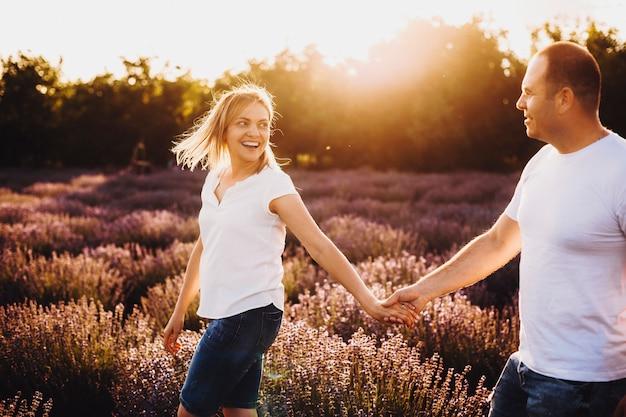 Mooie blanke vrouw met de hand van haar man die hem lachend bekijkt tijdens het wandelen in een lavendelveld tegen zonsondergang.
