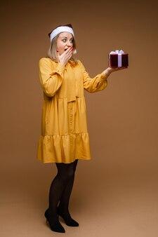 Mooie blanke vrouw met golvend blond haar houdt een klein cadeautje vast en verheugt zich, foto geïsoleerd op bruine muur