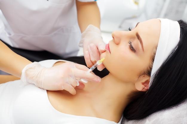 Mooie blanke vrouw met hyaluronzuur injectie in gezicht zone. mannelijke arts met spuit het vullen van het gezicht van de vrouw met collageen. verjongingstherapie concept.