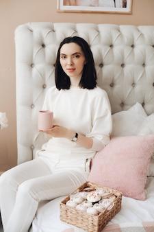 Mooie blanke vrouw met kort donker haar in een witte, knusse trui houdt een lekkere marshmallow vast en glimlacht