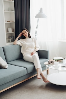 Mooie blanke vrouw met kort donker haar in een witte, knusse trui zit in de woonkamer en denkt na over haar toekomst