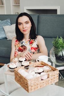 Mooie blanke vrouw met kort donker haar ontbijten met snoep, marshmallows en koekjes