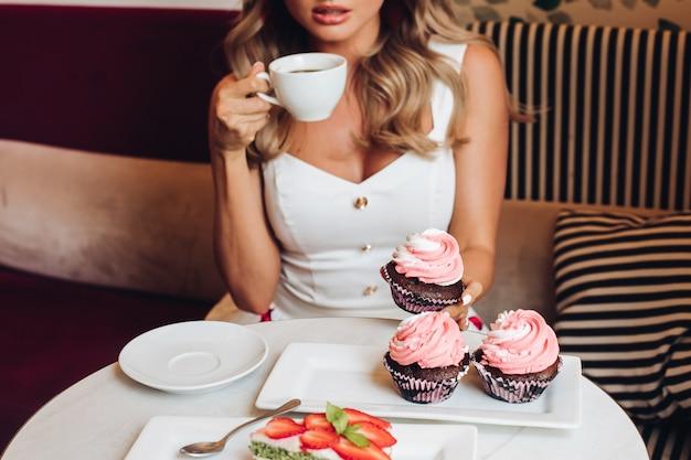 Mooie blanke vrouw met lang blond golvend haar zit op de bank, drinkt warme koffie of thee