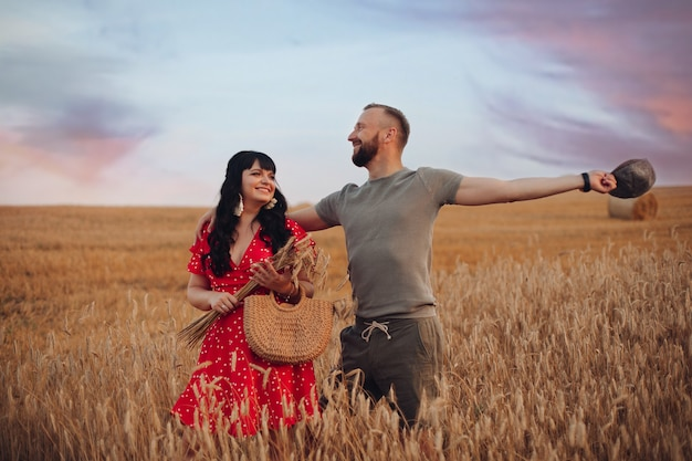 Mooie blanke vrouw met lang donker golvend haar in rode jurk met bloemen met mooie man in grijs t-shirt, hoed en korte broek