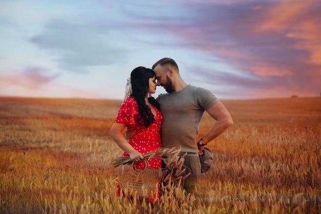 Mooie blanke vrouw met lang donker golvend haar in rode jurk met een tas en bloemen knuffels met haar mooie vriendje in grijs t-shirt, hoed en korte broek