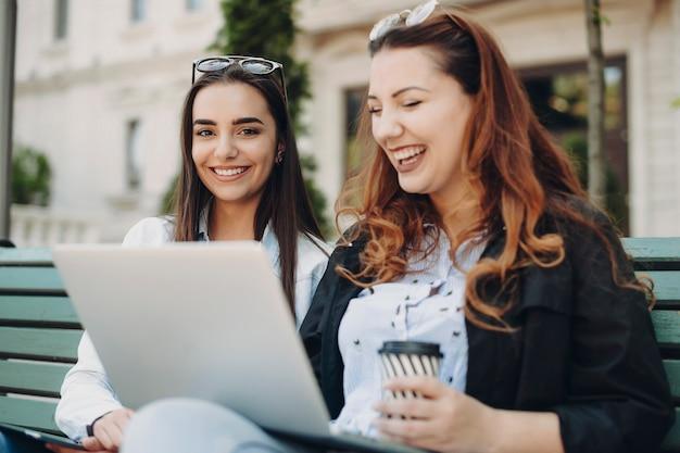 Mooie blanke vrouw met lang donker haar camera kijken lachen zittend op een bankje terwijl haar vriend laptop lachen kijkt.