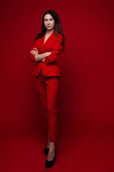 Mooie blanke vrouw met lang donker steil haar in een rood kantoorpak, zwarte schoenen