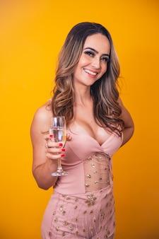 Mooie blanke vrouw op gele achtergrond met een glas champagne, vieren.
