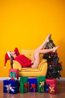 Mooie blanke vrouw op gele achtergrond verkleed als mama claus met verschillende kerstcadeautjes.