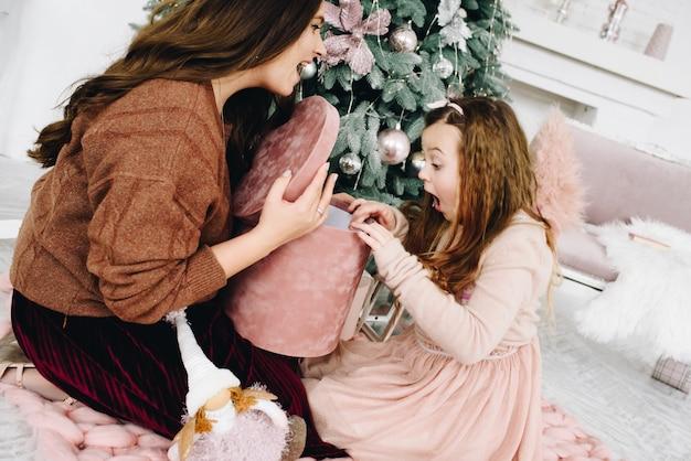 Mooie blanke vrouw toont haar gelukkig dochtertje haar kerstcadeau