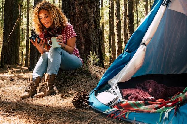 Mooie blanke vrouw van middelbare leeftijd die onder een dennenboom in het bos zit, gebruikt een mobiele technologietelefoon met internetverbinding om internet te zien en als freelance onafhankelijk te werken.