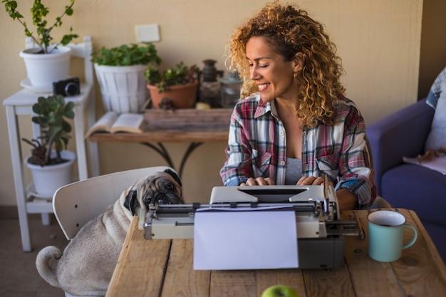 Mooie blanke vrouw van middelbare leeftijd gebruikt een oude typemachine om een blog of boek buiten te schrijven in de buurt van haar beste vriend een duidelijke nieuwsgierige hondmopshond gaat op de stoel bij de dame zitten