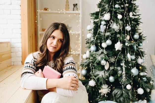 Mooie blanke vrouw zit naast mooie versierde kerstboom met een boek en dromen