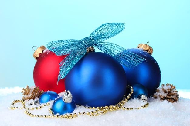 Mooie blauwe en rode kerstballen en kegels op sneeuw