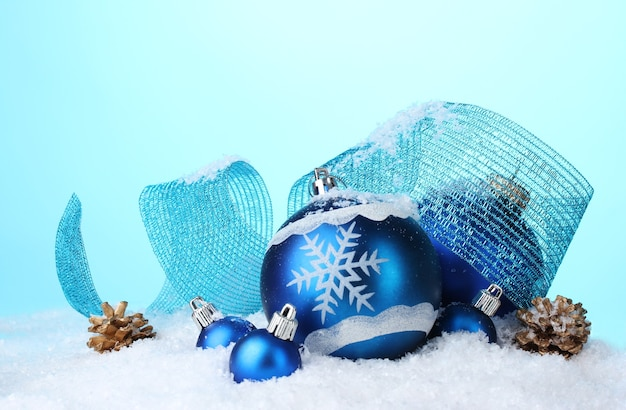 Mooie blauwe kerstballen en kegels in sneeuw op blauwe ondergrond