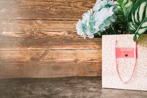 Mooie blauwe kunstbloemen in de papieren zak tegen houten achtergrond