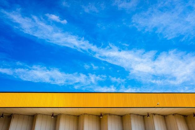 Mooie blauwe lucht met wolken, over een gele luifel van een fabriek.