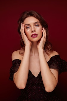 Mooie blauwogige jonge brunette dame feestelijke make-up en elegante kleding dragen, zacht haar gezicht met opgeheven handen vast te houden en te kijken