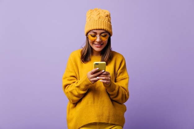 Mooie blije vrouw houdt van gele kleur en draagt een totale gele outfit. snapportrait van mooi meisje chatten in haar smartphone