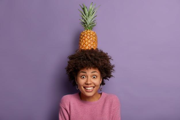 Mooie blije vrouw met afro-kapsel, houdt verse ananas met groene bladeren op het hoofd, vormt met zomerfruit