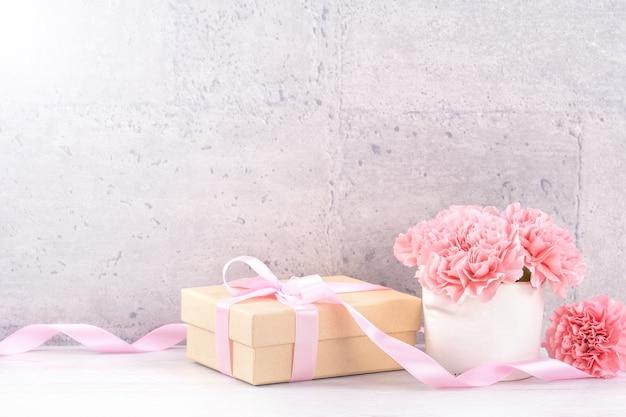 Mooie bloeiende anjers met roze lint doos geïsoleerd op een grijze achtergrond bureau, close-up, kopieer ruimte