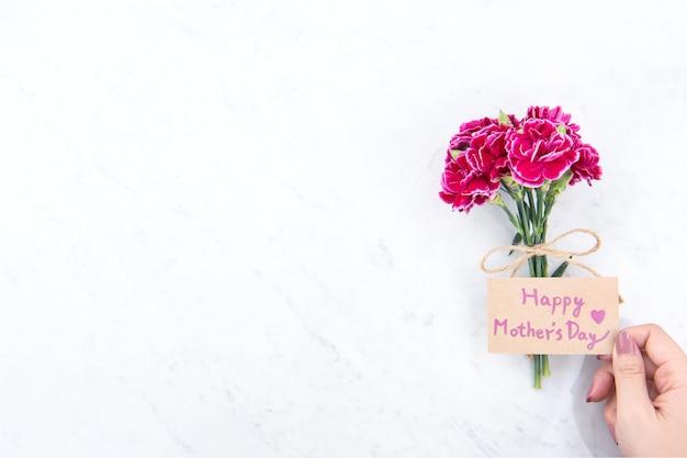 Mooie bloeiende anjers vastgebonden door touw kraft boog houden in de hand van de vrouw geïsoleerd op heldere moderne tafel, kopie ruimte, plat leggen, bovenaanzicht