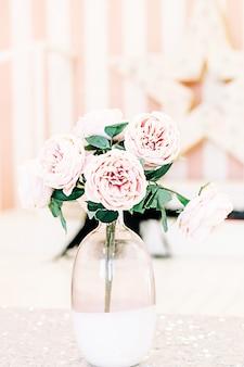 Mooie bloeiende roze rozen in vaas op een lichte achtergrond,