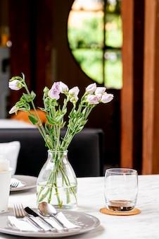 Mooie bloem in vaas op eettafel