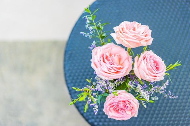 Mooie bloem in vaas op tafeldecoratie met uitzicht op de tuin