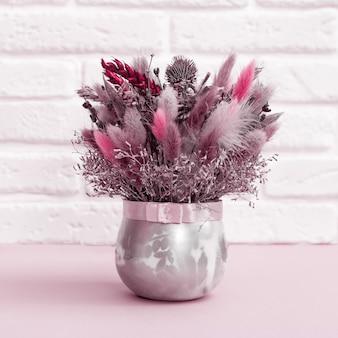 Mooie bloemen boeket roze en rood gekleurd met gedroogde planten, bloemen, gras. handgemaakte florale decoratie tegen witte bakstenen muur.