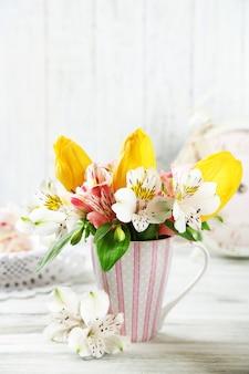 Mooie bloemen in beker, op houten achtergrond