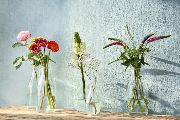 Mooie bloemen in glazen vazen op houten tafel en getextureerde muur