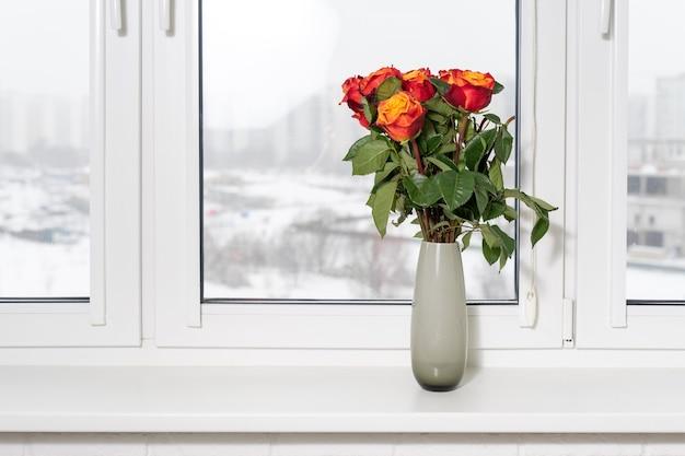 Mooie bloemen in vaas met licht van raam