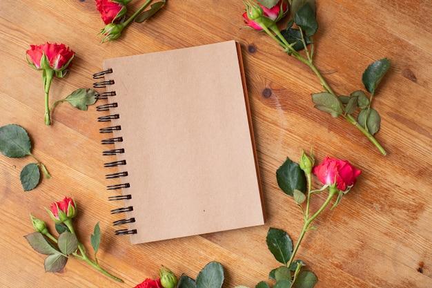 Mooie bloemen op de houten tafel met notebook. het werk van de bloemist. bloemen levering.