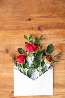 Mooie bloemen op een houten tafel met een envelop. het werk van de bloemist. bloemen levering.