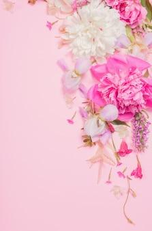 Mooie bloemen op roze papieren oppervlak