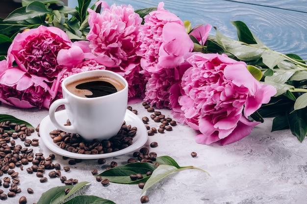Mooie bloemenpioenen naast een kopje koffie