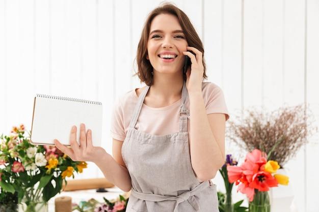 Mooie bloemist vrouw in schort in bloem werken en praten op mobiele telefoon met notities in de hand
