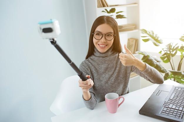 Mooie blogger zit aan tafel in lichte kamer en neemt selfie met een selfiestick