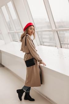 Mooie blonde aziatische vrouw in beige stijlvolle trenchcoat, jeans en rode baret vormt met kleine zwarte tas bij raam